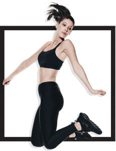 woman in fitness apparel jumping