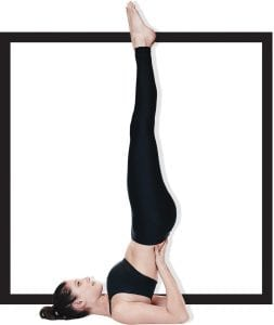 yoga model on back lifting body up with toes pointing toward sky
